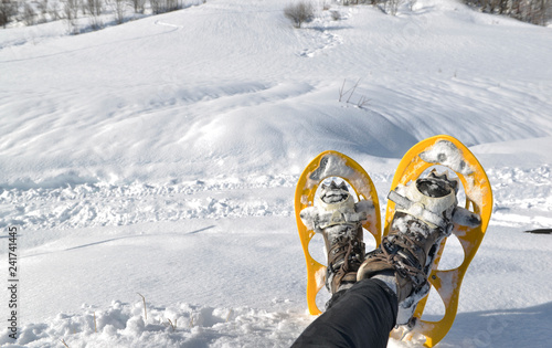 foot of woman with snowshoes sitting in the snow