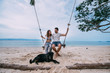 A loving couple is swinging on a swing and stroking a dog by the sea. Honeymoon by the ocean on a tropical island.