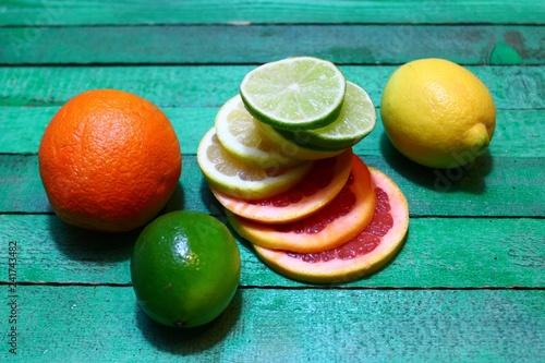 Fotografie, Obraz  Verschiedene Zitrusfrüchte auf grünen Holz