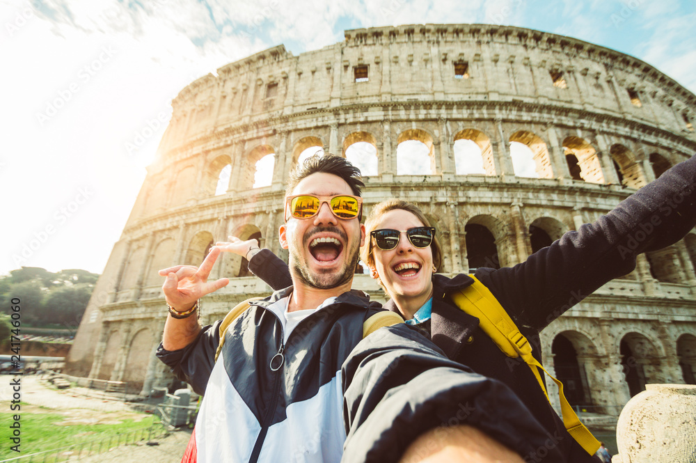 Fototapeta Happy caucasian couple is taking a selfie smiling at the camera in front of the colosseum in Rome