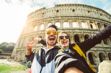 Happy caucasian couple is taking a selfie smiling at the camera in front of the colosseum in Rome