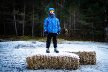 Boy On Top Of A Straw Bale  In...