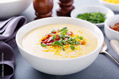 Potato cream soup with bacon, green onion and cheese close up