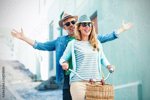 Photographie  Mature couple riding bicycle by building
