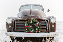 Front View Of An Old Rusty Truck With A Christmas Wreath