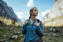 Female Hiker Standing In Field Against Mountains