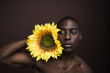 Man Holding Sunflower While Standing Against Brown Background