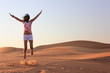 young woman jumping on the desert
