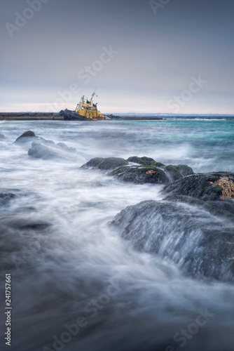 waves on the stones and flooded tug boat