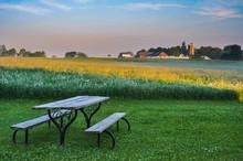 An Old Picnic Table In A Lawn Looking Toward A Farm Across An Alfalfa Field.