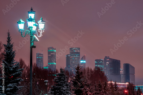 Tuinposter Stad gebouw Moscow City International Business Center. Modern skyscrapers in Moscow, tallest buildings in Europe. Winter night cityscape with lantern and snowy fir trees.