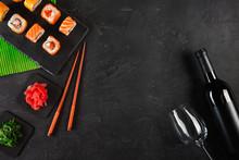 Sushi Set Sashimi And Sushi Rolls, Bottle Of Wine And A Glass Served On Stone Slate