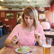 Face portrait of young happy European woman eating salad. Healthy lifestyle with green food.