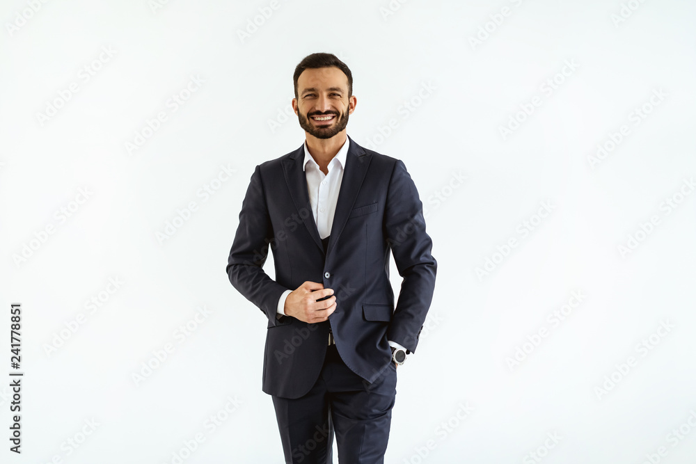Fototapeta The businessman in a beautiful suit standing on the white background