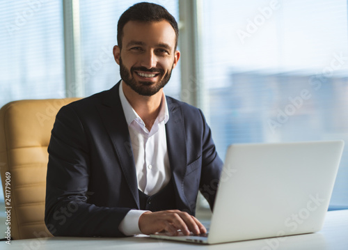 Fotografía  The handsome businessman with a laptop sitting at the desk