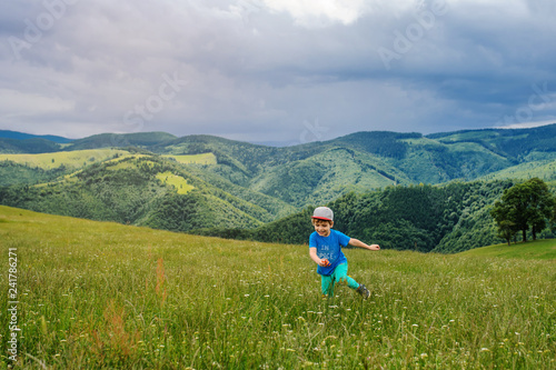 Photo  lateral view of a 6-years blond boy running on the top of the mountain