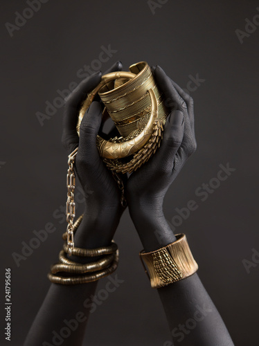 Black woman's hands with gold jewelry. Oriental Bracelets on a black painted hand. Gold Jewelry
