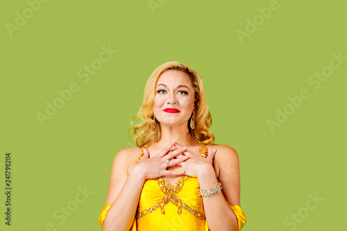 Dressed up blonde woman full of emotion, isolated on green studio background Canvas Print
