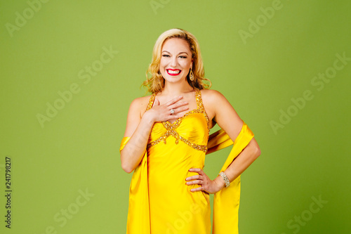 Photo  Glamorous blonde woman in yellow evening dress, isolated on peach colored studio
