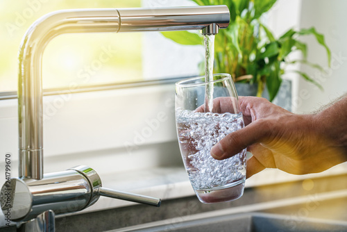 Fotografering  Hand holding a glass of water poured from the kitchen faucet