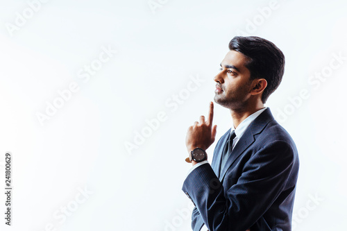 Fotografía  Profile of and interested man in business suit looking up with finger on chin, isolated on white