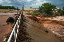 Muddy Flash Flood Running Through Culverts In Rural Desert Town