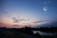 朝焼けが川面を染める朝の月