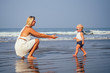 Mother and baby young woman teaching her sweet toddler daughter to walk her first steps on a sandy tropical sea beach. first step on the sandy beach near ocean in sunny morning.Mothers day concept
