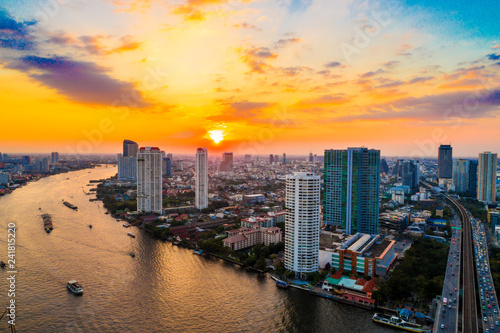 Sunset over the city building with transport road aerial view