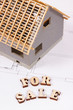 Inscription for sale and toy house under construction on electrical drawing, concept of selling and buying home or flat