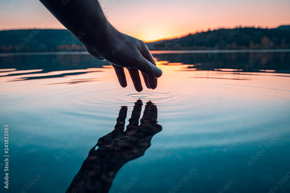 Fototapeta Finger touches surface of mountain lake. Hand reflection