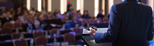 Presenter Presenting Presentation To Audience. Speaker Giving Speech To Audience In Conference Hall Auditorium. Defocused Blurred Conference Meeting People. Lecturer On Stage. Corporate Talk.
