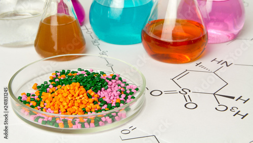 Cuadros en Lienzo  Plastic raw material in granules against the background of Chemical Laboratory and reagents