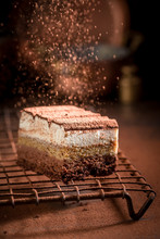 Falling Cocoa Powder On Tiramisu Cake On Metal Cooling Grid