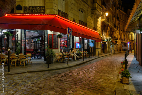 Fototapeta Cozy street with tables of cafe in Paris at night, France