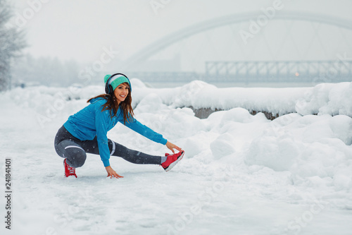 Poster Glisse hiver Young woman stretching legs on snowy day in the city