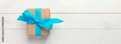 Fotomural Beautiful gift box with a blue bow on the white wooden table