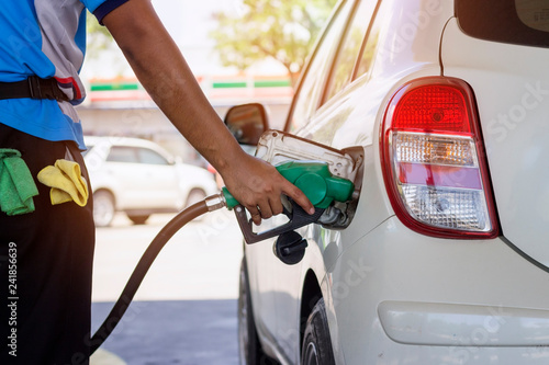 white car refueling gasoline by auto dispenser nozzle at petrol station with warm sunlight