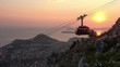 4K. Beautiful view of the sunset with the Dubrovnik cable car that going down. Orange colors. Down is the old town of Dubrovnik, Croatia