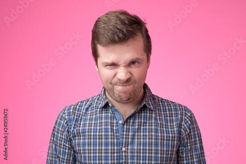 Portrait of an angry man on pink backfround. Fototapeta