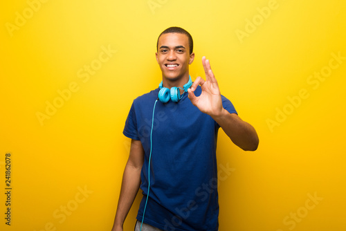 Fotografie, Obraz  African american man with blue t-shirt on yellow background showing an ok sign w