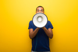 African american man with blue t-shirt on yellow background shouting through a megaphone to announce something