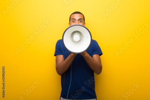 Tablou Canvas African american man with blue t-shirt on yellow background shouting through a m
