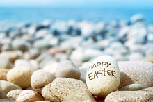 Easter Egg From A Stone With The Inscription Happy Easter On The Sea Pebble Beach.