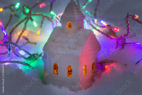 Fotografie, Obraz  A beautiful fabulous little white house with yellow lights in the windows and ga