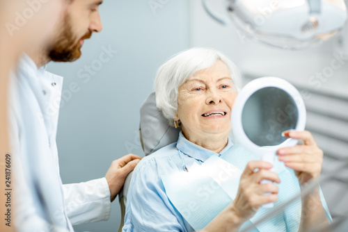 Fototapeta  Happy elderly woman enjoying her beautiful toothy smile looking to the mirror in