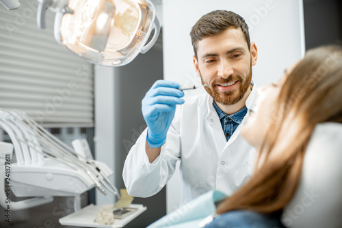 Handsome dentist making dental examination to a young woman patient in the dental office