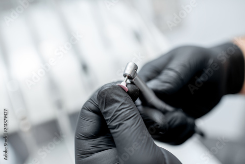 Fotografie, Obraz  Close-up of a dental drill with nozzle in the hands in black medical gloves