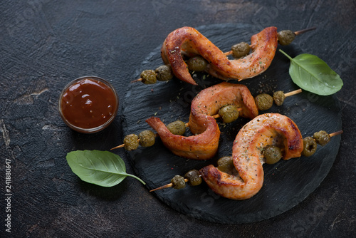 Wooden skewers with bbq pork loin and olives on a stone slate tray, dark brown stone background, horizontal shot