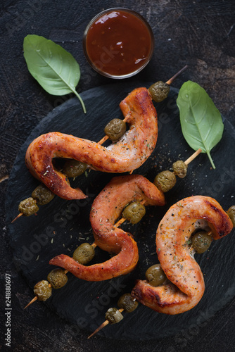 Close-up of barbecued pork loin and green olives on wooden skewers, flatlay, vertical shot